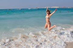 Woman juming on beach royalty free stock photography