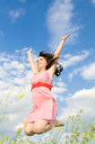 Woman in a jump. The young beautiful woman in a jump, hands are lifted upwards, on a background of the blue sky, smiles Royalty Free Stock Image