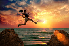 Woman jump. Rock to rock at sunset on sea Royalty Free Stock Photo