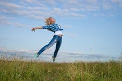 Woman jump in green grass field Stock Photos