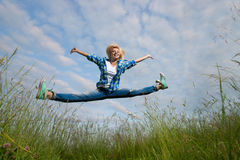 Woman jump in green grass field Stock Photos