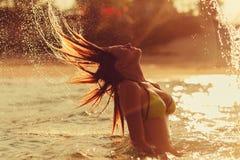 Woman jump hair water splash at sunset Royalty Free Stock Image
