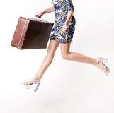 Woman in a jump in a hurry with a suitcase Stock Photography