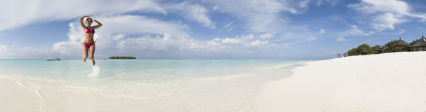 Woman jump in lagoon of Ihuru Island Maldives pano Stock Photography