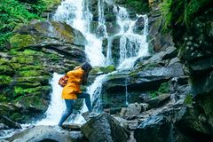 Woman jump from rock to rock in forest. water fall on background. Woman jump from rock to rock in forest in yellow raincoat. water fall on background royalty free stock photo