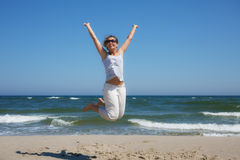 Woman in a jump shot on the beach of the Baltic sea Royalty Free Stock Photos