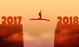 A woman jump between 2017 and 2018 years. Girl silhouette jumping over a gap between two rocky mountains Stock Photo