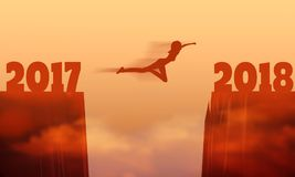 A woman jump between 2017 and 2018 years. Girl silhouette jumping over a gap between two rocky mountains Royalty Free Stock Photo