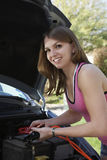 Woman With Jumper Cables By Car Stock Images