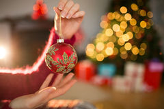 Woman in jumper holding red bauble Stock Photos