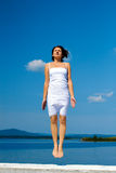 Woman is jumping against blue ocean Royalty Free Stock Photo