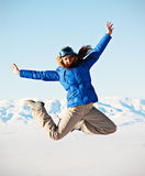 Woman jumping against snowy mountains Royalty Free Stock Photos