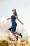 Woman jumping in the air. Young attractive woman jumping in the air looking very happy against a city sky background Royalty Free Stock Photos