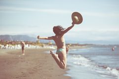 Woman jumping in the air on tropical beach,having fun and celebrating summer,beautiful playful woman jumping of happiness Stock Photo