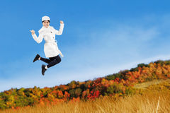 Woman jumping with an autumn jacket Stock Image