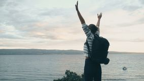 Woman jumping. Woman with backpack happily jumping near the sea coast stock footage