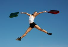Woman jumping with bags Stock Photography