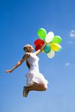 Woman jumping with balloons Stock Image