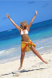 Woman jumping on the beach. Young woman jumping on tropical beach in pareo Stock Image