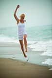Woman jumping in the beach Royalty Free Stock Photography
