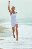 Woman jumping in the beach Stock Image