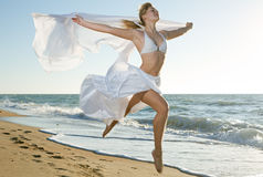 Woman jumping on the beach Royalty Free Stock Photography