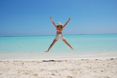 Woman jumping on beach. Young woman jumping on beautiful beach Stock Image
