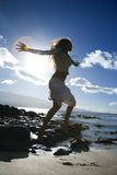 Woman jumping on beach Stock Image