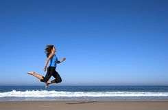 Woman jumping in the beach. Young woman running and jumping on the beach Royalty Free Stock Images