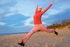 Woman jumping on a beach stock photo