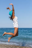 Woman jumping on a beach. Stock Image