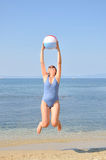 Woman jumping on the beach Stock Images