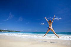 Woman jumping on the beach Stock Photo