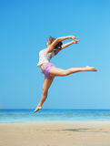 Woman jumping on the beach Stock Image