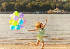 Woman jumping on the beach with colored polka dots balloons Stock Photography