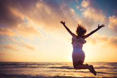 Woman jumping at the beach Stock Image