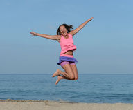 Woman jumping on beach. Mature woman jumping in air on sandy beach on sunny day Royalty Free Stock Photography
