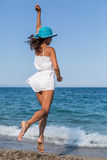 Woman jumping on a beach. Stock Photos