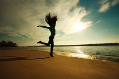 Woman jumping on the beach on sunny sky background Royalty Free Stock Photography