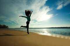 Woman jumping on the beach on sunny sky background, sunrise Stock Images