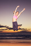 Woman jumping on the beach at sunset Stock Photos