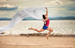 Woman jumping on the beach with a white tissue Royalty Free Stock Photography