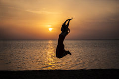 Woman jumping beautiful silhouette against the sea and dawn stock images