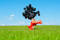 Woman jumping with black balloons in hands Royalty Free Stock Image