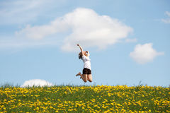 Woman jumping on blossom meadow. Stock Images