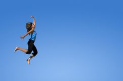 Woman jumping in a blue sky. Young woman jumping over a blue sky royalty free stock photos