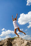 Woman jumping on blue sky background Royalty Free Stock Photography