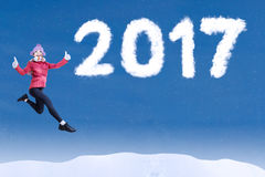 Woman jumping on blue sky with 2017. Image of attractive woman jumping on the blue sky while wearing winter clothes with number 2017 Stock Photography