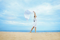 Woman jumping with cloth on a beach Stock Photos