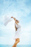 Woman jumping with cloth on a beach Royalty Free Stock Photography